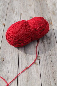 Rotes Wollknäul mit rotem abgehenden Faden