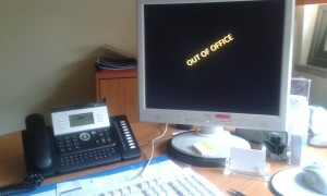 Schreibtisch dessen PC den Bildschirmschoner Out of Office anzeigt