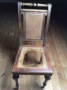 Holzstuhl mit Sitzfläche aus Flechtwerk. Dies hat ein Loch.